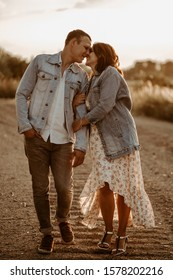 Happy young couple kissing at sunset. Girl in dress.jeans style