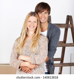 happy young couple with ladder renovating home