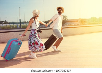 Happy young couple landed at the airport, arrived at the destination of vacation