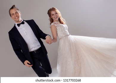 Happy young couple laughing and dancing together. The couple in the Studio a light background. Boyfriend and girlfriend, costume and wedding dress