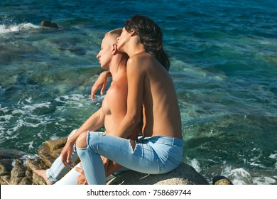 Happy young couple laughing and hugging on the beach. Couple. Fashion photo. Love story. Sensual. Dreaming concept. Dream. Lifestyle. Life. Man and woman sitting stone. Sea background. Sea beach. Sexy
