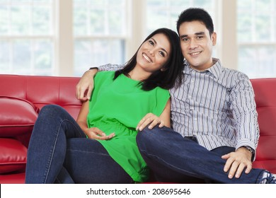 Happy young couple laughing and looking at camera in a living room