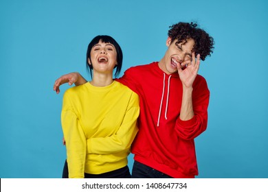 happy young couple laughing over blue background