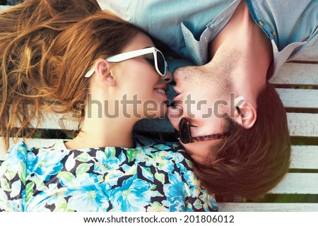 Happy young couple laying on white floor and have a sweet kiss, wearing retro clothes and sunglasses.