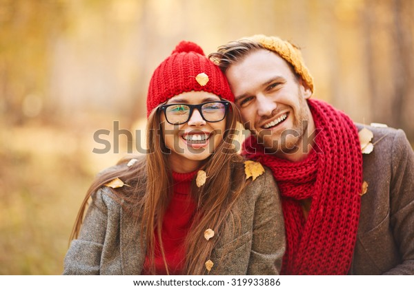 Happy young couple in leaf fall enjoying autumn