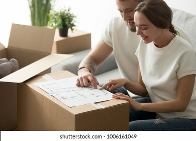 Happy young couple looking at blueprint planning new home interior design settling in, homeowners talking about remodeling ideas, discussing house architectural plan moving in apartment with boxes