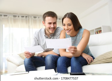 Happy young couple looking and checking bills on a couch at home
