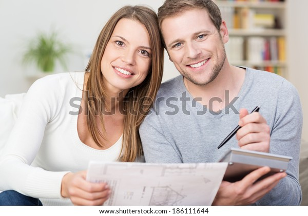 Happy young couple looking at a diagram of a new product together with a calculator to see if they can afford it or if it would be suitable for their house