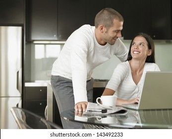 Happy Young couple looking at each other while using laptop in modern kitchen