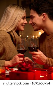 Happy young couple in love bonding, holding glasses, drinking wine, enjoy tender moment together celebrating Valentines day having romantic dinner date with candles sit at home table or in restaurant.