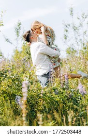 A happy young couple in love embraces each other tenderly looking at each other in nature under the bright summer sun