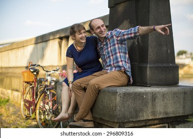 Happy young couple. Couple in love emotionally talking sitting on the urban stone waterfront.