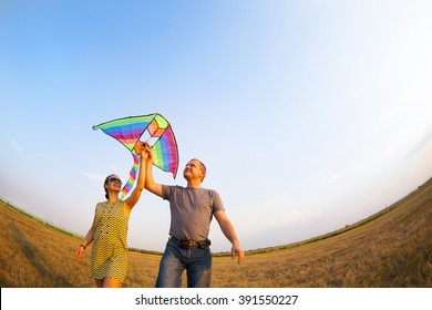 Happy young couple in love with flying a kite