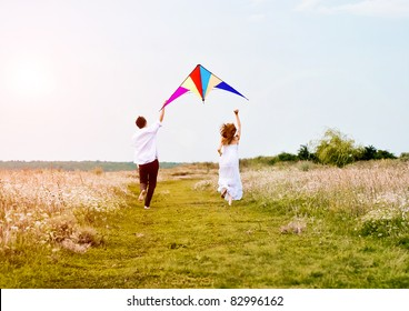 Happy young couple in love flying a kite