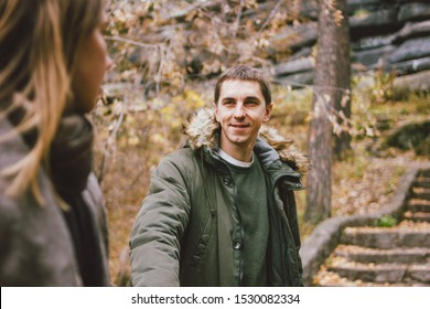 Happy young couple in love friends dressed in casual style walking together on nature park forest in the cold season, family advenure travel