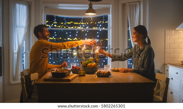 Happy Young Couple in Love Have Romantic Dinner, Toasting Each other with Glasses of Wine, Eating Tasty Meal in the Kitchen, Celebrating, Talking. Beautiful Lovely Husband and Wife Have Romantic Time