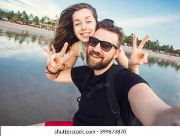 Happy young couple in love having fun and taking selfie portrait on beach of Bali on the background of blue sea