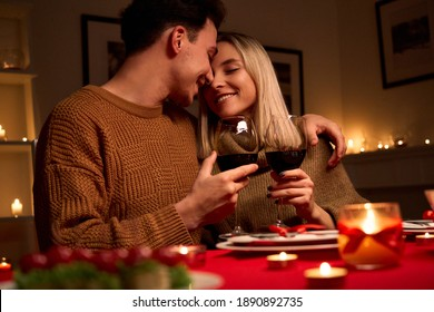 Happy young couple in love hugging holding glasses, drinking wine, celebrating Valentines day dining at home together, having romantic dinner date with candles sitting at table, embracing and bonding. - Shutterstock ID 1890892735