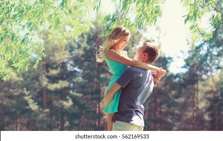 Happy young couple in love hugging enjoys spring day, loving man holding on hands his woman carefree together outdoors walking at park