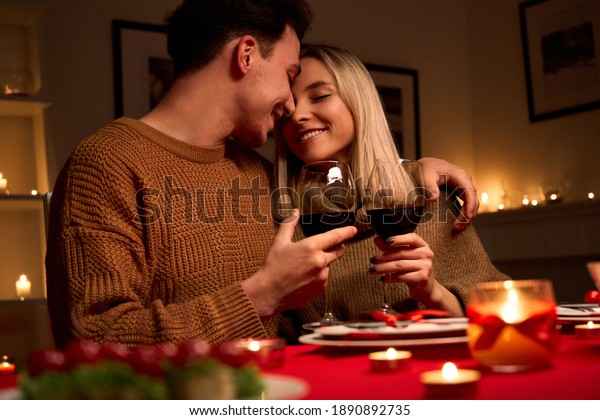 Happy young couple in love hugging holding glasses, drinking wine, celebrating Valentines day dining at home together, having romantic dinner date with candles sitting at table, embracing and bonding.