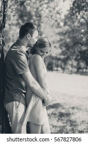 Happy young couple in love, man hugging woman, retro black and white photo