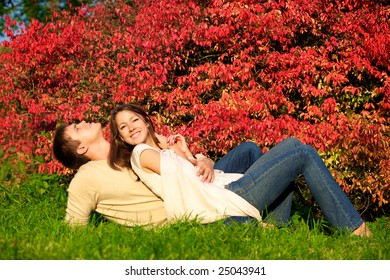 Happy young couple in love meeting in the autumn park with red leaves
