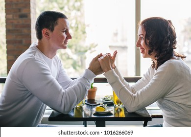 Happy young couple in love sitting in cafe. Young man holding girl's hands