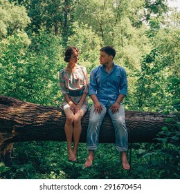 Happy young couple in love sitting on fallen trunk tree and looking at each other in summer park