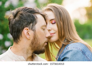 Happy young couple in love smiling and enjoying a walk in the summer Park. Romance and the concept of rest. Girl affectionately call concerns his cheeks and girlfriend feels butterflies in his stomach