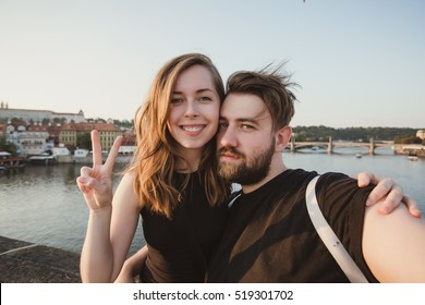 Happy young couple in love takes selfie portrait on Charles Bridge, Prague, Czech Republic. Pretty tourists make funny photos for travel blog in Europe.
