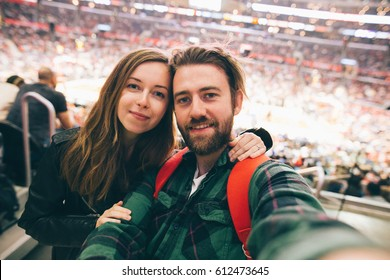 Happy young couple in love taking selfie self-portrait at basketball game on a stadium