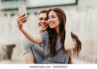 Happy young couple in love teenagers friends dressed in casual style making selfie at the street