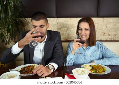 Happy young couple in love toasting with wine while having a lunch at Chinese restaurant