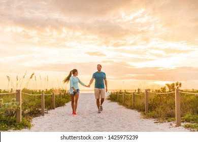 Happy young couple in love walking on romantic beach stroll at sunset. Lovers holding hands on Florida vacation holidays. People walking on summer evening lifestyle.