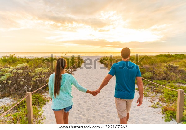 Happy young couple in love walking on romantic evening beach stroll at sunset. Lovers holding hands on summer holidays in Florida beach vacation destination. People walking from behind.