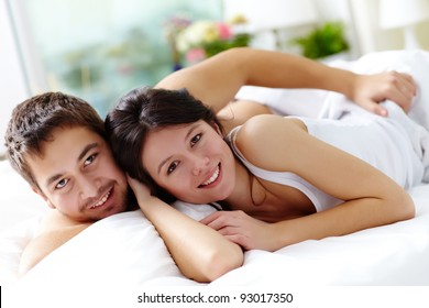 Happy young couple lying in bed and looking at camera with smiles