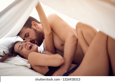 Happy young couple lying and hugging in bed at home