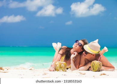 happy young couple lying on a tropical beach in Barbados and drinking a coconut cocktail