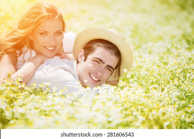 Happy, young couple lying on front in chamomile, daisy field.Copy space, lens flare