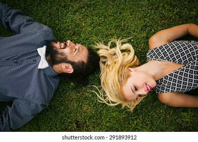 Happy young couple lying on grass