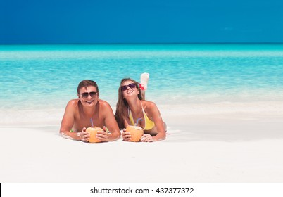 happy young couple lying on a tropical beach in Cayo Largo and drinking a coconut cocktail