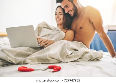 Happy young couple lying on a bed with computer - Beautiful married couple watching role games sex video on laptop laughing together - People, sexual, technology concept - Soft focus on sheets
