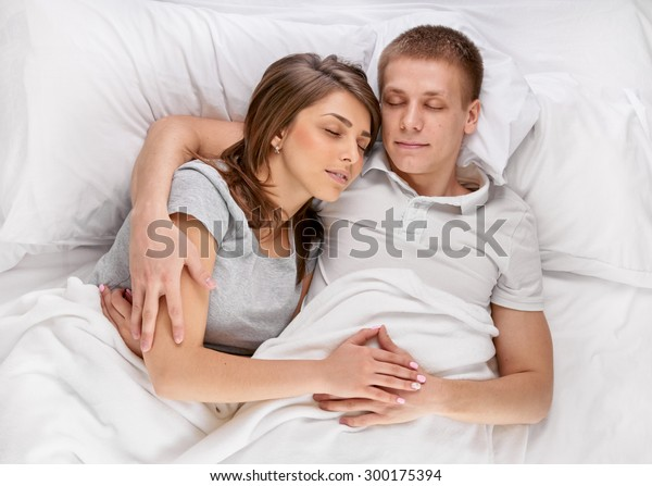 Happy young couple lying and sleeping in bed, shot from above