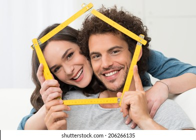 Happy Young Couple Making House Shape With Folding Ruler