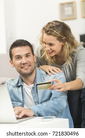 Happy young couple making purchase on internet