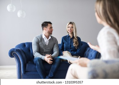 Happy young couple making up at therapy session with psychologist. Psychological counseling.