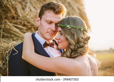 Happy young couple: man in suit with bow tie and woman with fresh flowers wreath hug near a stack of hay in sunset. Shallow focus. Back light, lens flare.