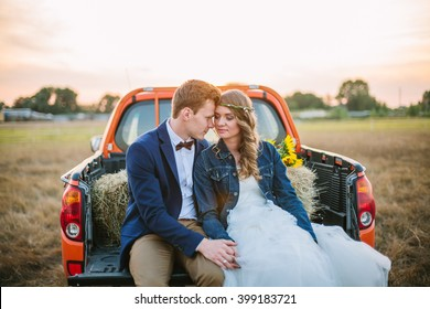Happy young couple: man in suit and bow tie and woman with fresh flowers wreath and wedding dress hug sit in truck trunk in sunset. Shallow focus. Back light, lens flare.