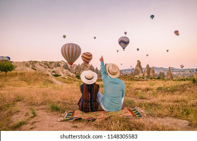 Happy young couple man and woman on vacation Turkey watching the Sunrise with millions of hot air balloons in Kapadokya, Cappadocia Turkey