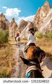 happy young couple man and woman Horseback riding through the national Park in Cappadocia, Turkey, People riding horse trough the mountains of Kapadokya Turkey